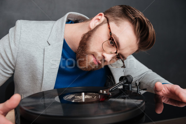 Concentrated bearded young man in glasses using turntable Stock photo © deandrobot