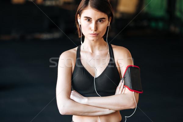 Nő atléta fülhallgató áll keresztbe tett kar tornaterem Stock fotó © deandrobot