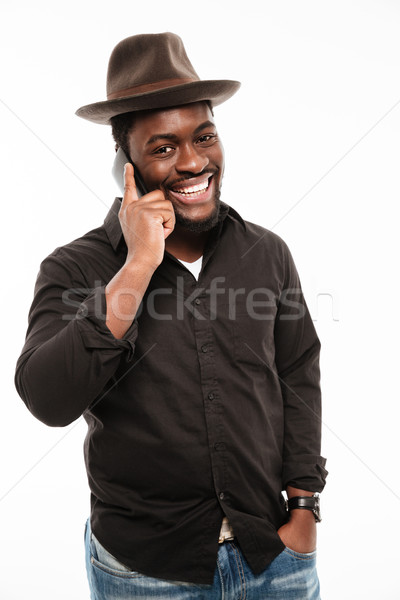 Stock photo: Cheerful young african man talking by phone.