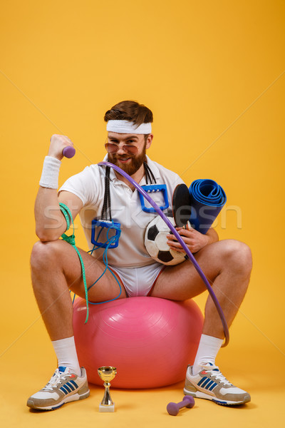 Portrait of a sports man sitting on a fitness ball Stock photo © deandrobot