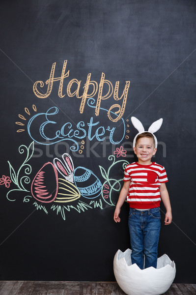 Happy little boy wearing rabbit ears and standing inside big cracked eggshell Stock photo © deandrobot