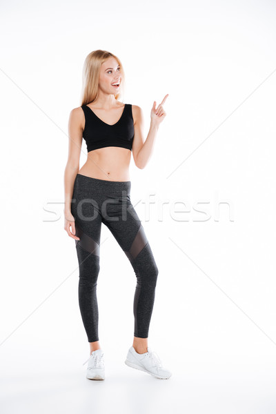 Smiling pretty fitness woman pointing to copyspace. Stock photo © deandrobot