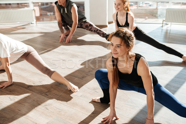 Group of happy young people working out and practicing yoga Stock photo © deandrobot