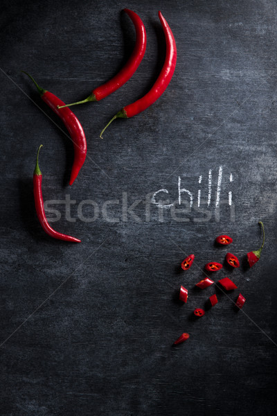 Cut chilli pepper over dark background. Stock photo © deandrobot
