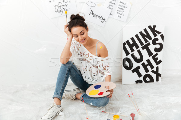 Cheerful young lady artist sitting on floor over white background Stock photo © deandrobot