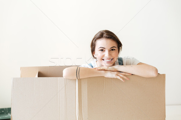 Happy woman peeking out from box Stock photo © deandrobot