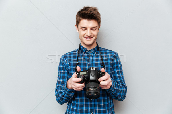 Stock photo: Pretty man looking images at his camera