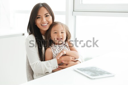 Happy young mom with little daughter using laptop writing notes Stock photo © deandrobot