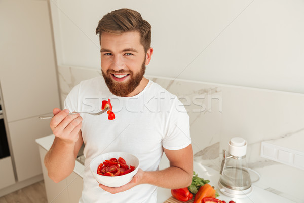 Smiling bearded man eating vegetables from plate Stock photo © deandrobot