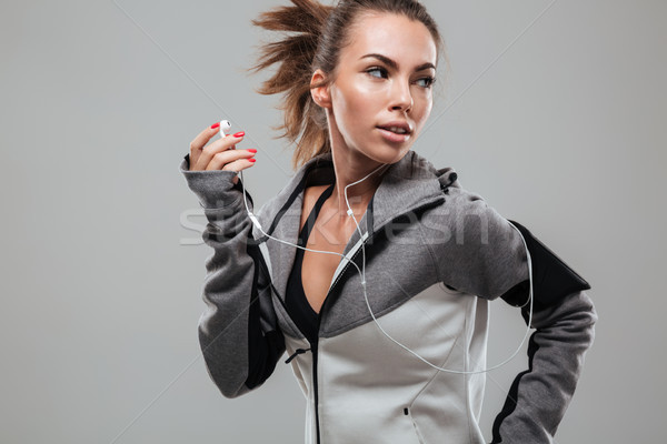 Female runner in warm clothes running in studio Stock photo © deandrobot