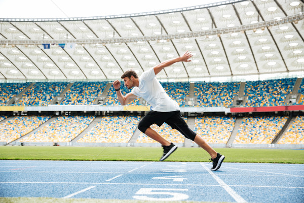 Side view of a sport man running on a racetrack Stock photo © deandrobot