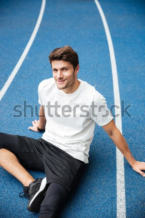 Concentrated young sports man sitting at the stadium Stock photo © deandrobot