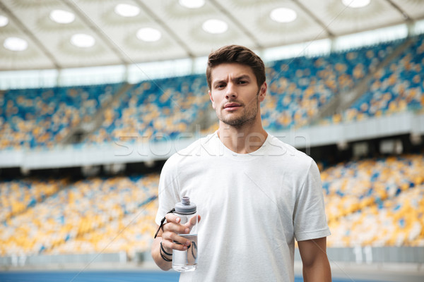 Young male athlete holding bottle of water Stock photo © deandrobot