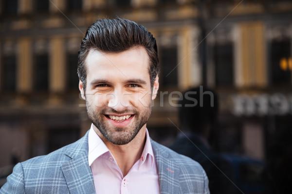 Mosolyog jóképű férfi kabát néz kamera közelkép Stock fotó © deandrobot