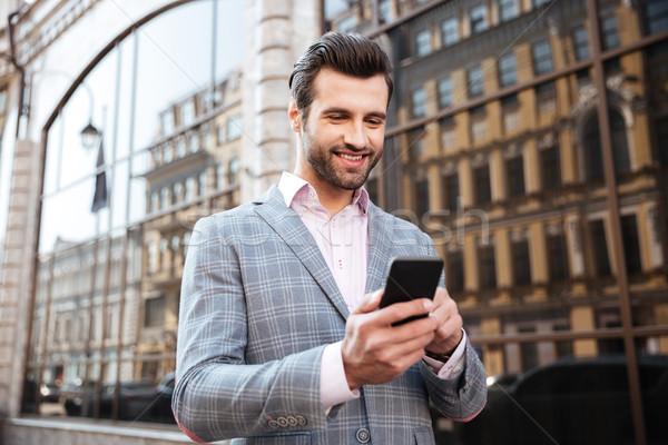 Portrait souriant jeune homme veste regarder téléphone portable Photo stock © deandrobot