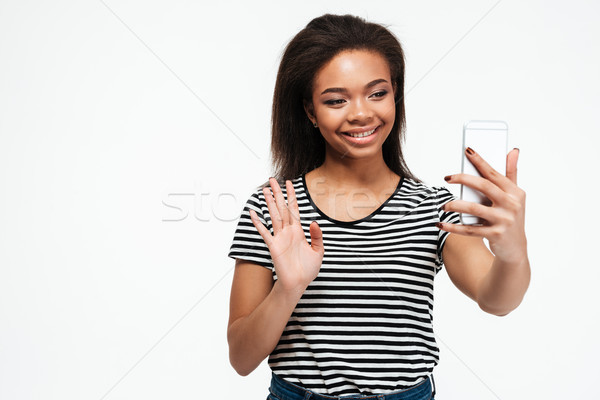 Cheerful young african lady talking by phone and waving. Stock photo © deandrobot