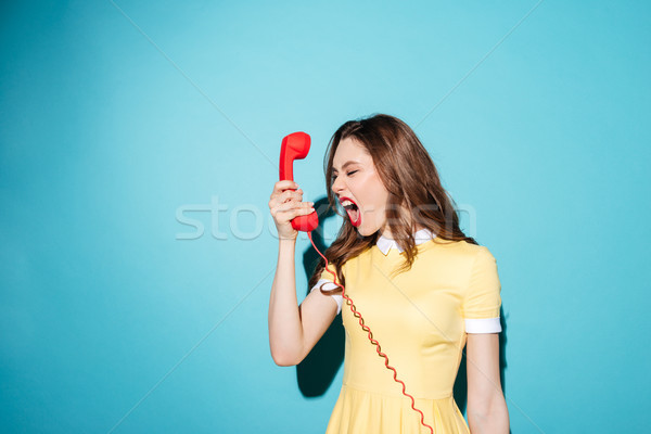 Angry furious girl in dress screaming at retro telephone tube Stock photo © deandrobot