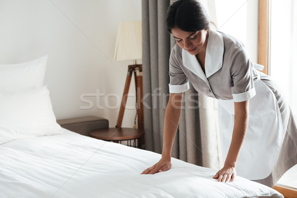 Maid setting up white bed sheet in hotel room Stock photo © deandrobot