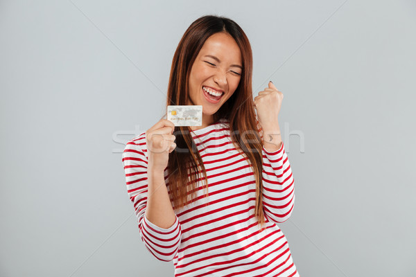 Happy asian woman in sweater rejoice and holding credit card Stock photo © deandrobot