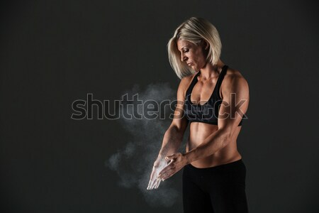Portrait of a muscular sportswoman clapping hands Stock photo © deandrobot