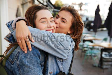 Close-up photo of two  happy pretty woman friends in jeans jacke Stock photo © deandrobot