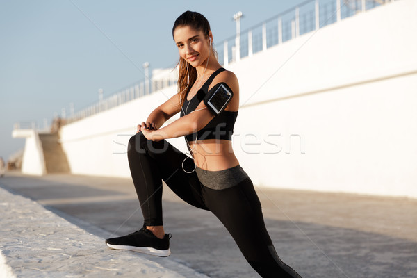 Stock photo: Cheerful young sports woman listening music