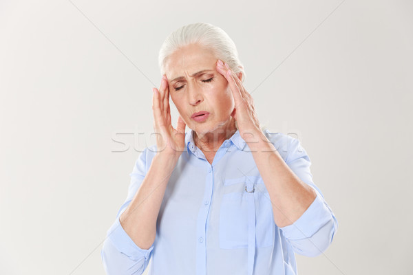 Elderly lady with headache Stock photo © deandrobot