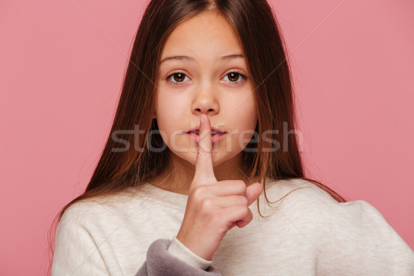 Calm beautiful girl looking camera andmaking silence gesture isolated Stock photo © deandrobot