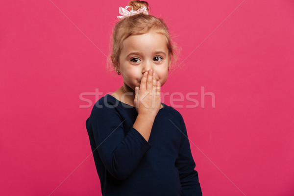 Pretty young blonde girl covering her mouth and looking aside Stock photo © deandrobot