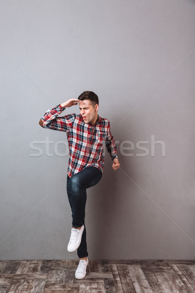 Full length image of Pleased man in shirt and jeans Stock photo © deandrobot
