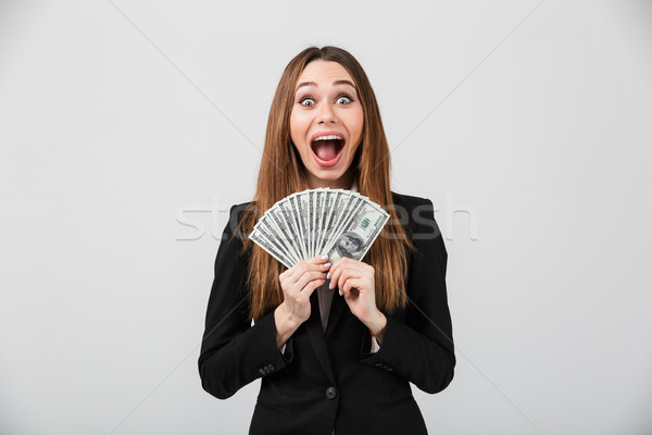 Happy young lady looking camera and showing cash dollars isolated Stock photo © deandrobot