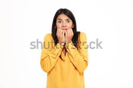 Shocked scared young lady in yellow shirt standing isolated Stock photo © deandrobot