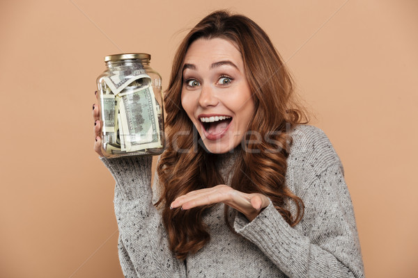 Happy brunette girl in gray jersey holding bank with dollar cash Stock photo © deandrobot