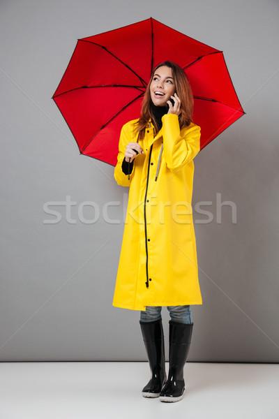 Teljes alakos portré derűs lány esőkabát áll Stock fotó © deandrobot