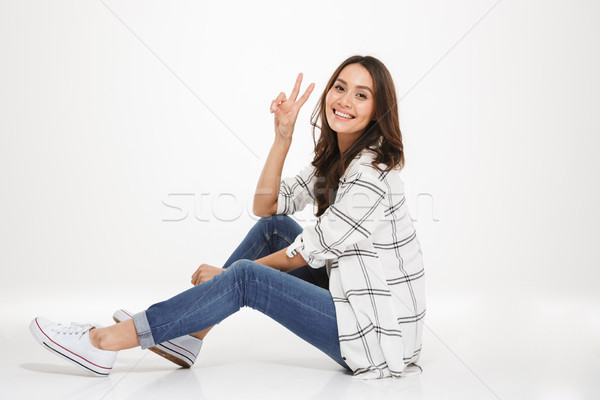 Horizontal image of cute young woman with brown hair sitting in  Stock photo © deandrobot