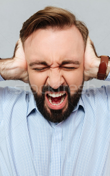 Vertical image of screaming bearded man in business clothes Stock photo © deandrobot