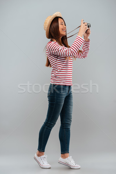 Full length image of cheerful asian woman in sweater Stock photo © deandrobot