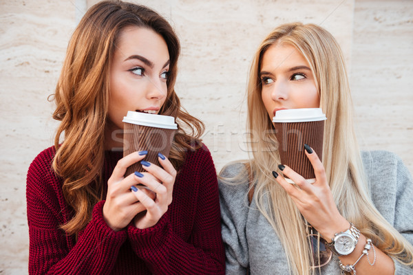 Portrait of a two pretty smiling girls holding coffee cups Stock photo © deandrobot