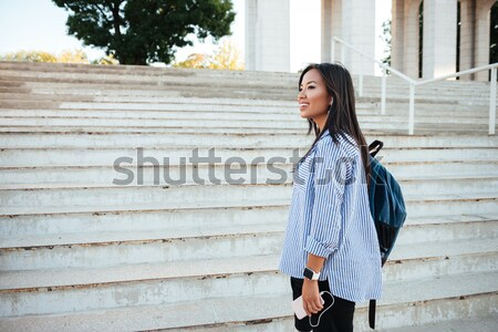 Portrait of beautiful smiling asian woman with backpack going up Stock photo © deandrobot