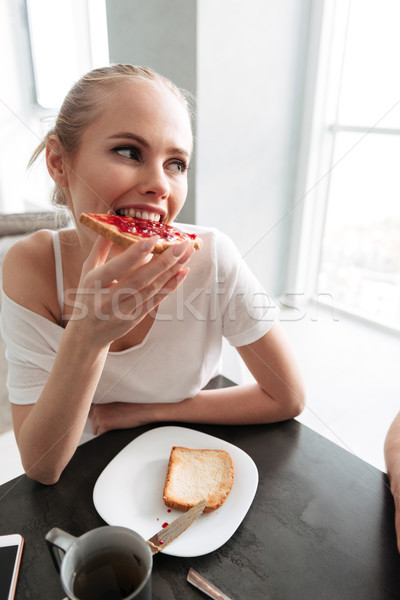Smiling lady eating bread with jam and looking aside Stock photo © deandrobot