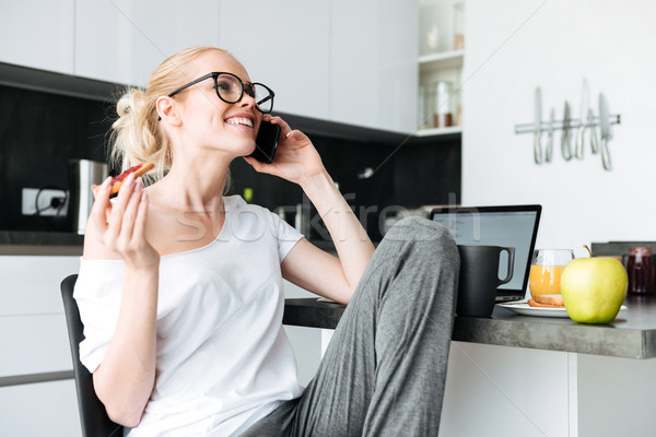 Cheerful lady laughing while talking on smartphone in kitchen Stock photo © deandrobot