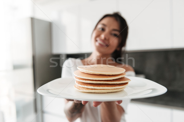 Happy young woman holding pancakes. Stock photo © deandrobot