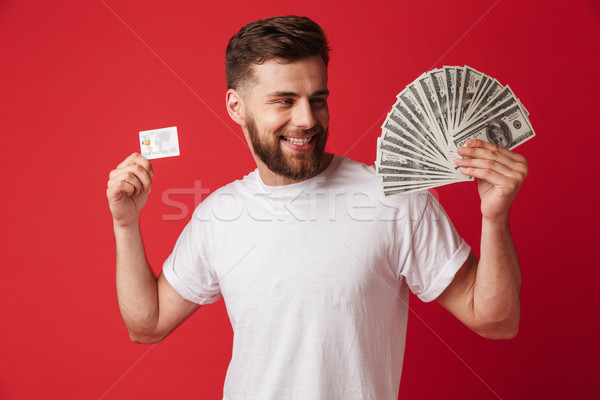 Excited young man holding money and credit card. Stock photo © deandrobot
