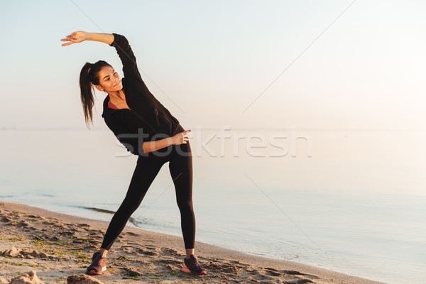 Pretty young sportswoman doing stretching exercises Stock photo © deandrobot