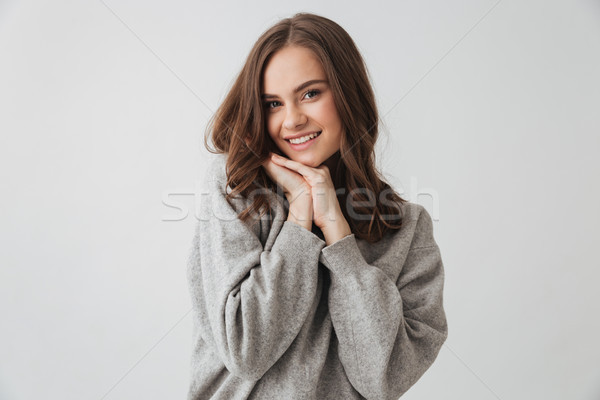 Pleased lovely woman in sweater posing with arms near face Stock photo © deandrobot