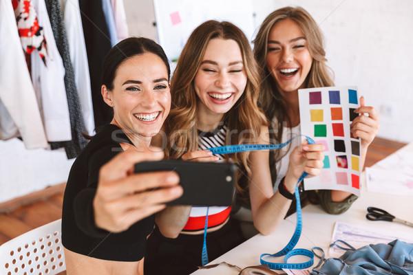 Három boldog fiatal nők ruházat dolgozik együtt dolgozni Stock fotó © deandrobot