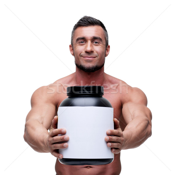 Happy muscular man holding holding jar with protein Stock photo © deandrobot