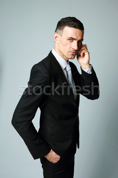 Confident businessman talking on his mobile phone on gray background Stock photo © deandrobot