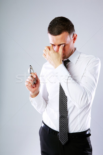 Portrait of a businessman holding glasses and rubbing his eyes on gray background Stock photo © deandrobot