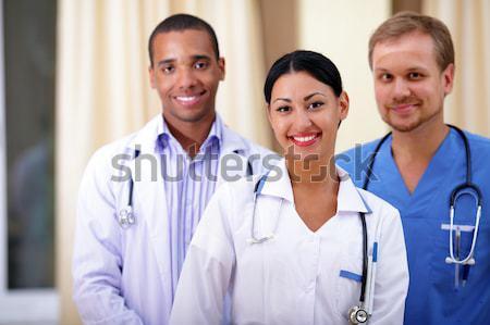 Stock photo: Multi-ethnic team of confident happy doctors with their happy patient